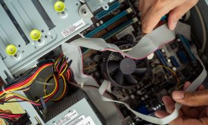 Kuala Lumpur, Malaysia - May 22, 2020:  Cleaning and fixing the personal computer (PC) with a vacuum cleaner. Computer service and maintainance.